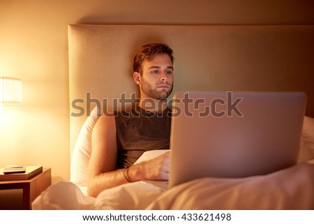 Handsome young man lying in bed at home at night, with his laptop on his legs, watching his favourite series for entertainment - stock photo