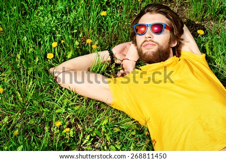 Handsome young man lying on a grass and smiles dreamily. Summer rest, vacation. - stock photo