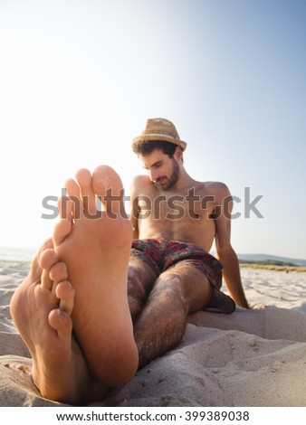 Handsome young man lying on the beach at summer - stock photo