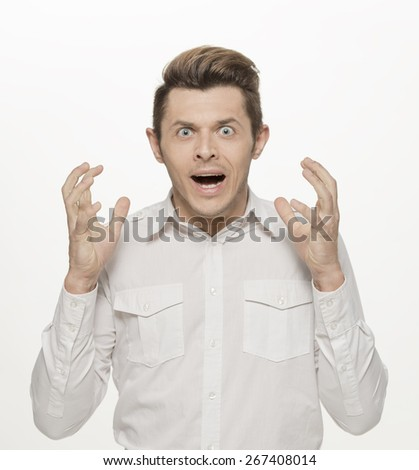 Handsome young man making furious face, with hands on head, isolated on white - stock photo