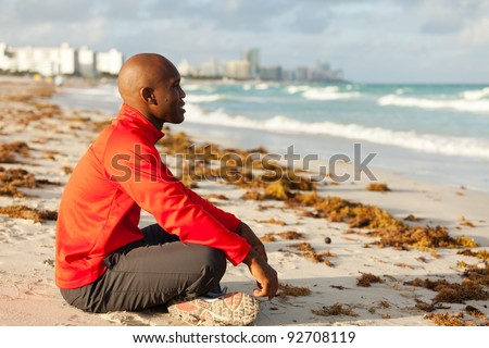 Handsome young man meditating in South Beach in Miami. - stock photo