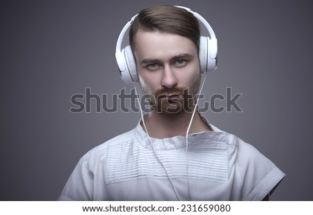 Handsome young man on a gray background with headphones. Favorite music. Relaxed listening to music - stock photo