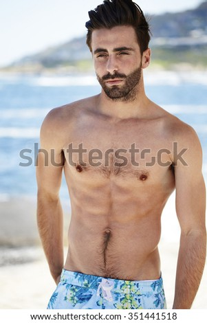 Handsome young man on beach, looking away