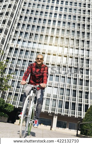 Handsome young man on bike in the city. Bicycle concept