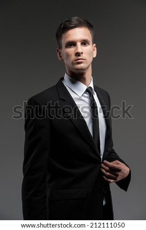 Handsome young man on grey background. side view of man in black suit looking into camera  - stock photo