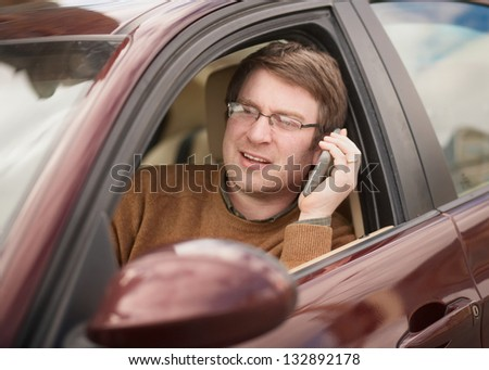 Handsome young man on phone while driving car
