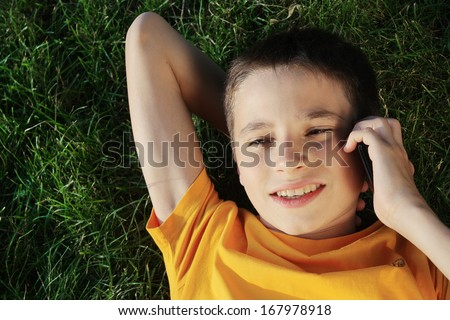 handsome young man on the grass talking cellphone - stock photo