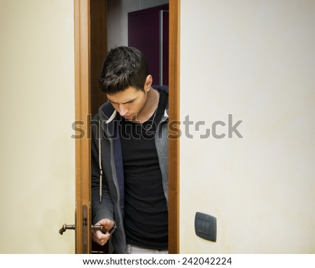 Handsome young man opening door to enter into a room, looking down at handle - stock photo