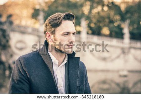 Handsome young man outdoor in winter fashion, wearing black coat and woolen scarf in city park
