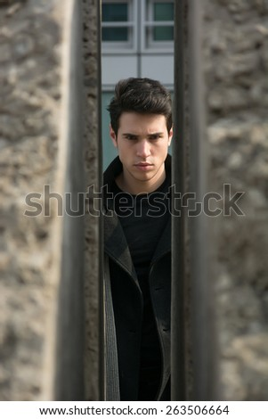 Handsome young man outdoor seen between two walls or stones, looking at camera with stern expression - stock photo