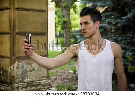 Handsome young man outdoors taking photo or self portrait with cell phone's camera - stock photo