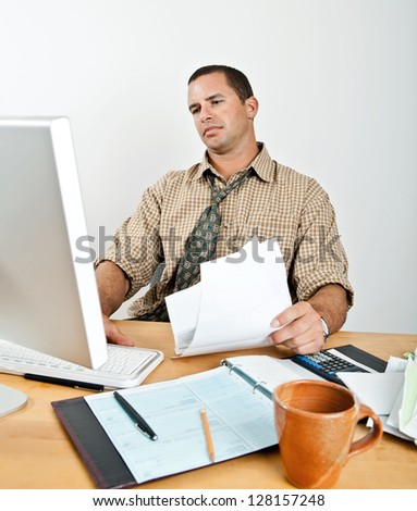 Handsome young man paying bills and reviewing finances. Seated at desk with computer and open checkbook. - stock photo