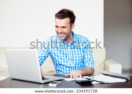 Handsome young man paying online using a laptop - stock photo