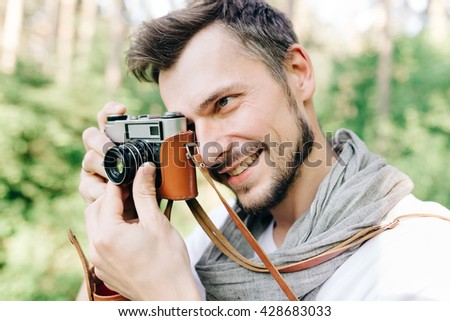 Handsome young man photographed on a retro camera on a forest, close emotional portrait