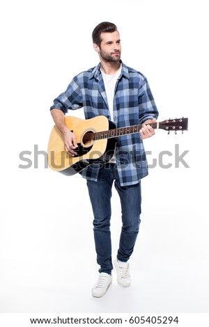 Handsome Young Man Playing Acoustic Guitar And Looking Away Isolated On White