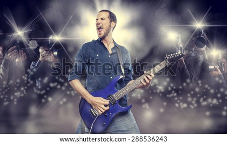 handsome young man playing electric guitar in front of photographers paparazzi