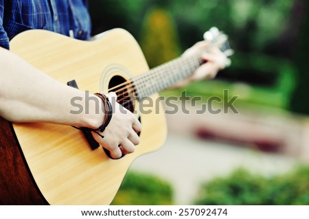 Handsome young man playing guitar - stock photo