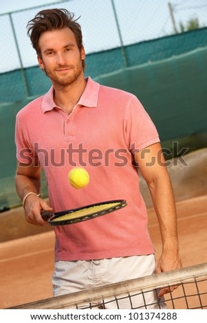 Handsome young man playing tennis on hard court, smiling, looking at camera.