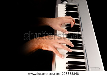 handsome young man playing the piano isolated in dark background