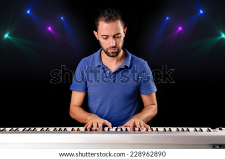handsome young man playing the piano isolated in dark background - stock photo