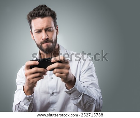 Handsome young man playing with his smartphone - stock photo