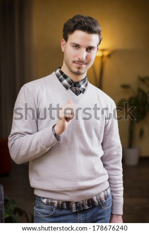 Handsome young man pointing finger at himself, smiling. Indoors shot inside a house - stock photo
