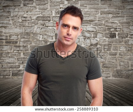 Handsome young man portrait over vintage wall background. - stock photo