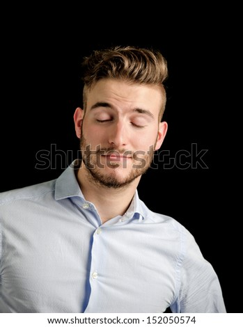 Handsome young man portrait with confident expression, grinning with eyes closed - stock photo