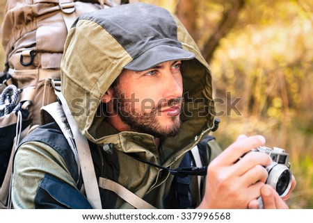 Handsome young man portrait, with vintage camera. Hooded guy hiking in the forest. Active lifestyle, tourism in nature. - stock photo