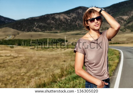 Handsome young man posing on a road over picturesque landscape. - stock photo
