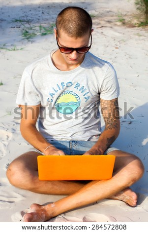 Handsome young man posing on the  beach and working on laptop on internet. Freelance work,travel concept,hike man,social network,man with computer on the beach,working on the beach of tropical island - stock photo
