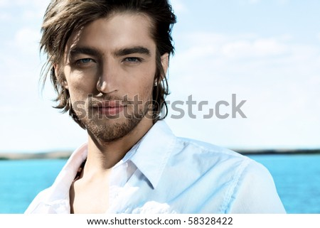 Handsome young man posing over sea and blue sky. - stock photo