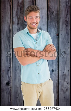 Handsome young man posing with arms crossed against grey wooden planks - stock photo