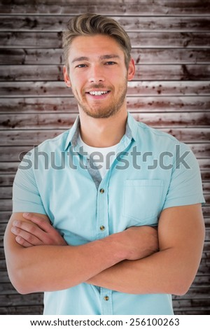 Handsome young man posing with arms crossed against wooden planks
