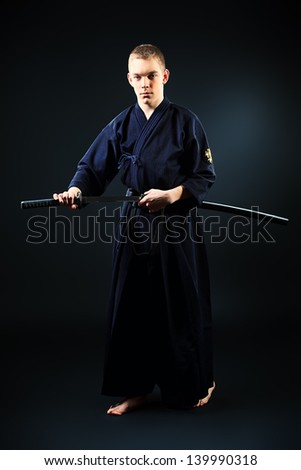 Handsome young man practicing kendo. Over dark background. - stock photo