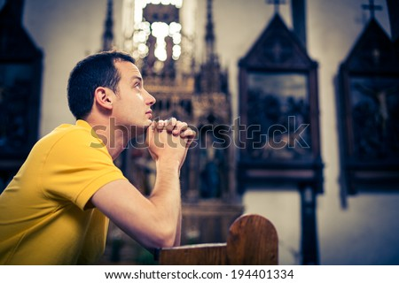 Handsome young man praying in a church - stock photo