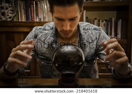 Handsome young man predicting the future by looking into black crystal ball - stock photo