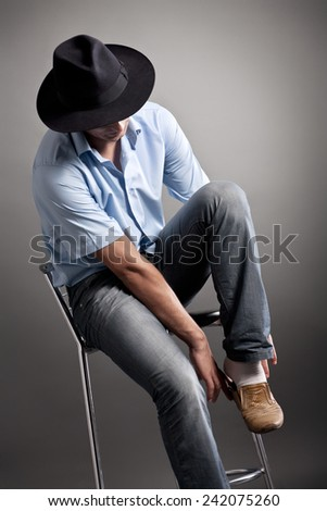 Handsome young man puting on shoe studio portrait - stock photo