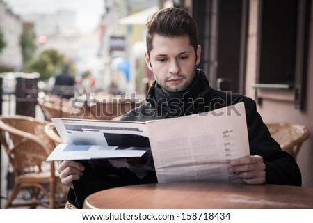 handsome young man reading a magazine in a cafe on the street - stock photo