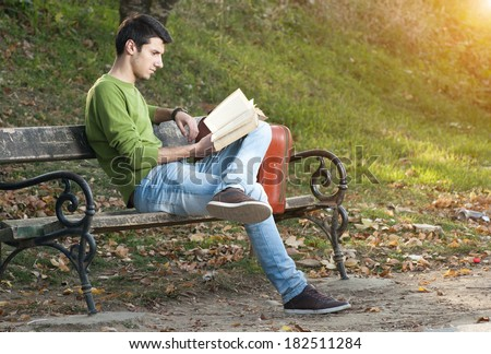 Handsome young man reading book on bench in the park  - stock photo