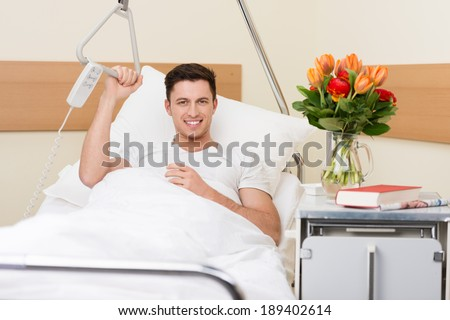Handsome young man recuperating in a hospital sitting up in bed with a cheerful smile and a big bouquet of flowers on the night stand - stock photo