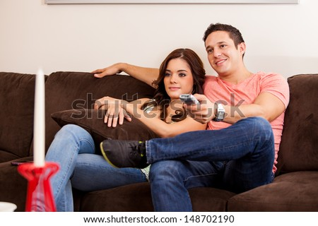 Handsome young man relaxing and watching TV with his girlfriend - stock photo