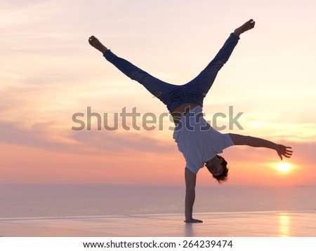handsome young man relaxing and working on laptop computer at home balcony while looking sunset - stock photo