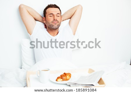 Handsome young man relaxing in bed - stock photo