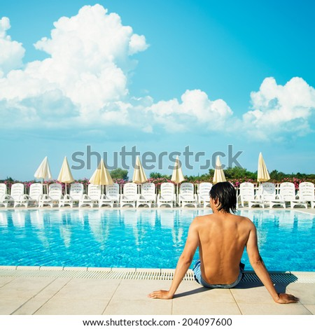 Handsome Young Man Relaxing near the Pool Outdoors. Healthy Lifestyle Concept. Summer Vacation. Copy Space. - stock photo