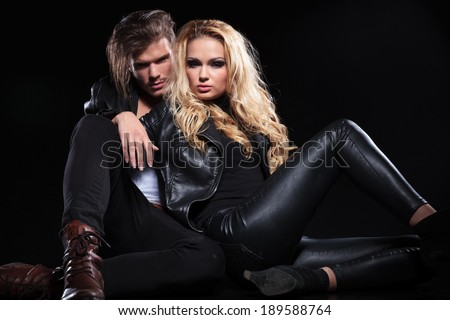 handsome young man relaxing on the floor with his girlfriend and looking into the camera . on black background