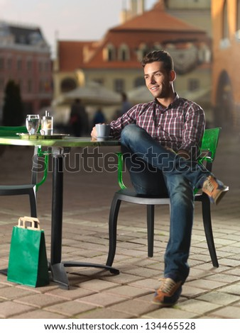 handsome young man resting on a coffee after a shopping session in downtown - stock photo
