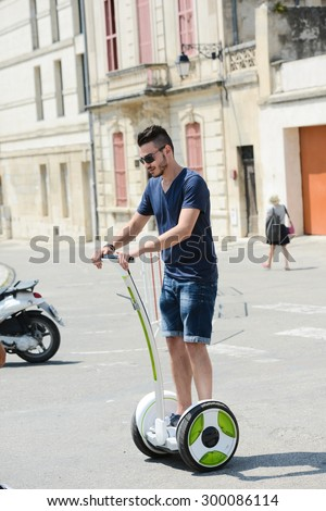 handsome young man riding segway gyropode electric two wheels vehicle on a sightseeing tour - stock photo
