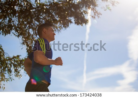 Handsome young man running at a park. Backlit with low angle, copy space and lens flare - stock photo