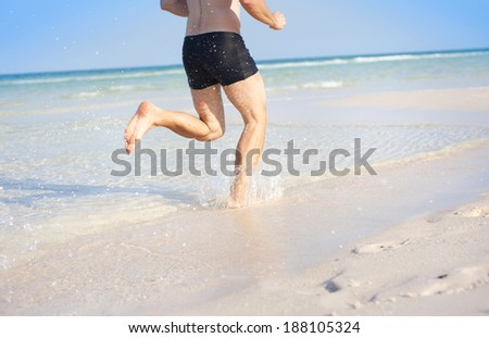 Handsome young man running at paradise beach in Phu quoc island, south of vietnam - stock photo